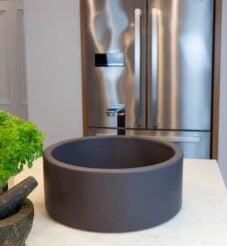 Dark matt grey circular sink fitted onto a white marble worktop.