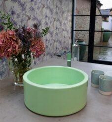 Light green circular sink set of a light grey worktop.