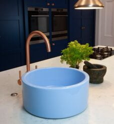 Light blue circular sink fitted onto a white marble worktop with navy blue kitchen setting.