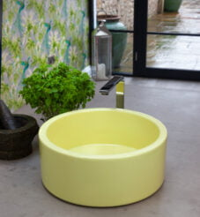 Bright yellow coloured sink with a vase of flowers on a grey worktop.