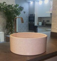 Pink mottle sink sat on a dark grey worktop, with the sleek, white kitchen in the background.