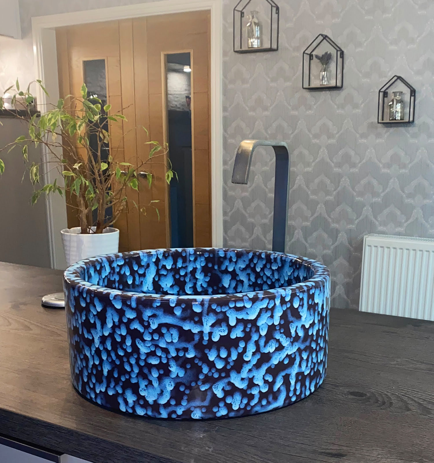 Electric blue and purple mottle kitchen sink, situated on a dark grey worktop.
