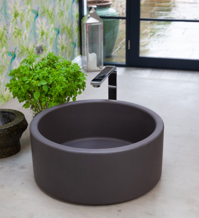 Grey kitchen sink sat on a light grey marble worktop with a plant beside it.