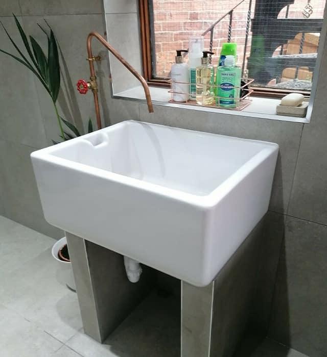 Belfast sink used in dark grey-themed bathroom setting.