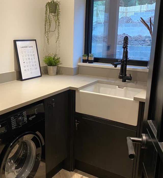 Utility room with dark cup boards and white worktops and walls, with a washing machine and a large Belfast sink.