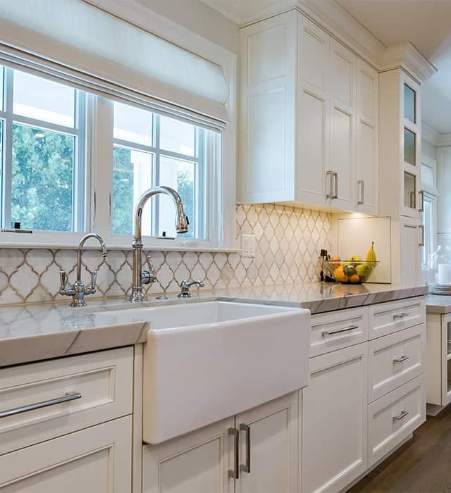 White themed kitchen with pattered splashback, large white sink with traditional fixtures.