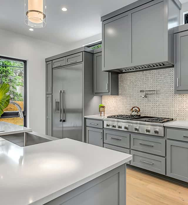 Luxurious grey kitchen setting with a patterned splashback.