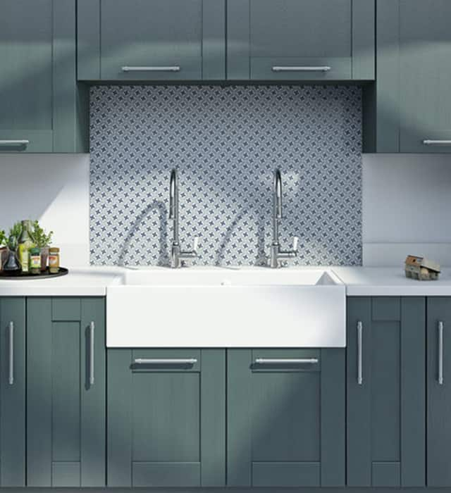 Double bowl sink in a grey/green kitchen setting with a patterned backsplash..